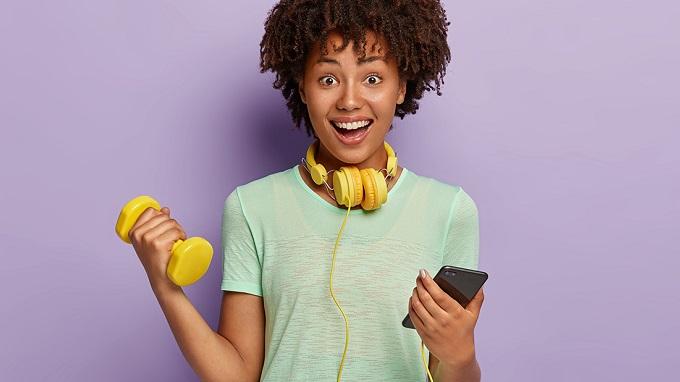 Frau mit Kopfhörer, Hantel und Smartphone